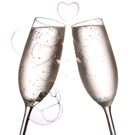 champagne flute: two glasses of chilled champagne with a beautiful heart shaped bubble.