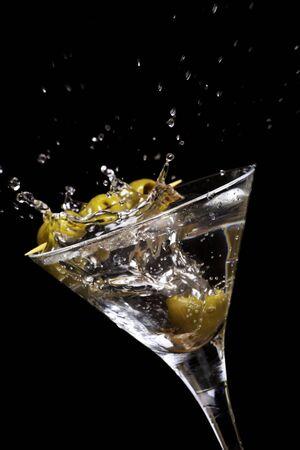 martini splash: Delicious fresh olive cascading into martini glass Stock Photo