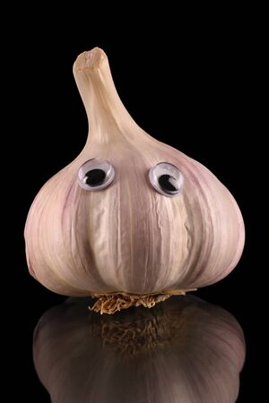 Garlic bulb with funny face on a reflective surface, isolated on a black background. Stock Photo