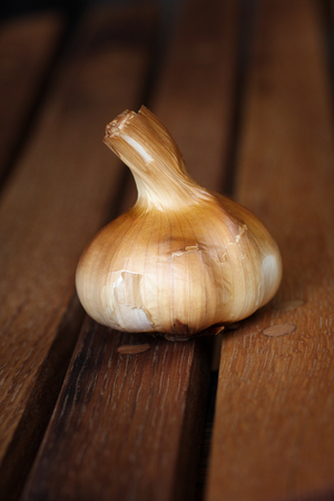 deliciously: Deliciously smoked garlic bulb taken against a rustic old barrel background Stock Photo
