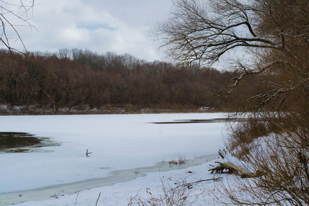 Winter forest on the banks of the river, covered with snow and ice Stock Photo