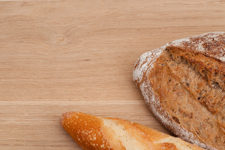 French bread, loaf and ciabatta on a wooden background with space for text