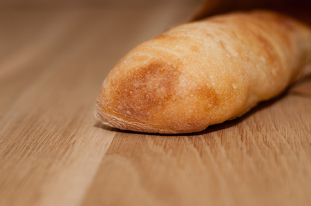 Bread of ciabatta with a crispy, golden crust on a light wooden table in a paper bag. View from above and from the side. Stock Photo