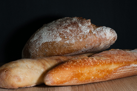 French loaf, bread and ciabatta on a black background