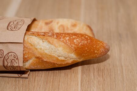 Two fresh baguettes, a French loaf and Italian ciabatta with a golden crust on a wooden background.