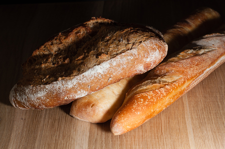 French and Italian bread on a wooden background with space for text, top view.