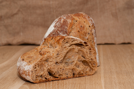 Cut into halves of black French bread on a background of a wooden board and burlap