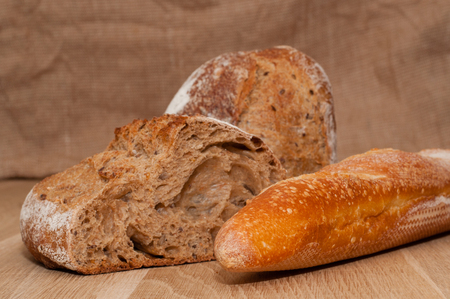 Cut into halves of black French bread and French loaf on the background of a wooden board and burlap