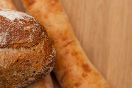 dark French bread and two baguettes on a wooden board Stock Photo