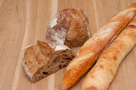 Sliced bread and two baguettes on a wooden board background