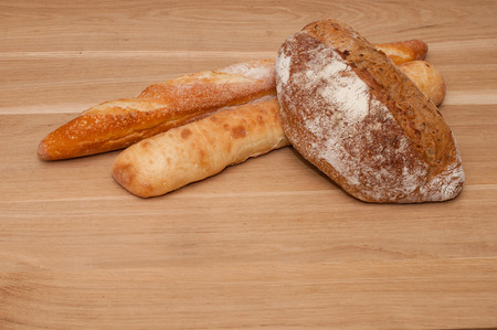 Black bread, ciabatta and French loaf on a light wooden board