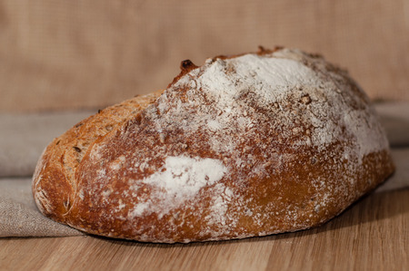 French bread sprinkled with flour, against a background of linen cloth and burlap
