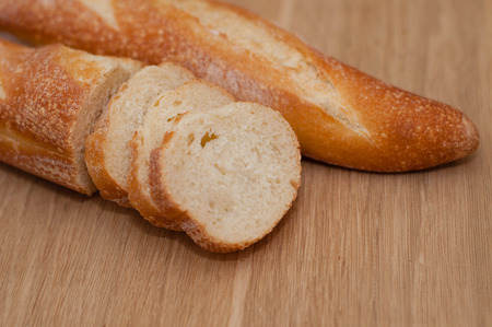 French loaf, sliced, on a wooden board with space for text