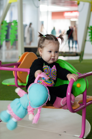 Little baby girl playing cheerfully at a playground in a shopping center.