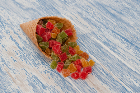 Sweet candied fruit in a waffle cone on a rustic background. Candied dried apricots, pineapple and papaya cubes lie on a blue background. Copy space for text.