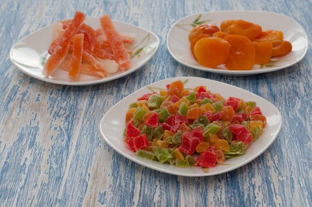 Candied dried apricots, papaya, multi-colored pineapple cubes lie in white dishes on a blue wooden background