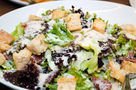 Salad with croutons, grated cheese, greens and cabbage. Salad in a white dish on the table.