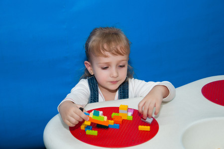 Child girl playing at the game table in the designer Stock Photo