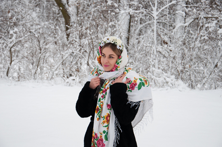 Happy girl in traditional Ukrainian clothes walking in the park in winter 스톡 콘텐츠
