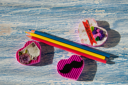 Pink handmade hearts on a blue wooden vintage background and colored pencils. Work on creating things handmade