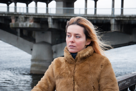 Emotional woman in the background of the bridge. The concept of emotion is sadness, joy