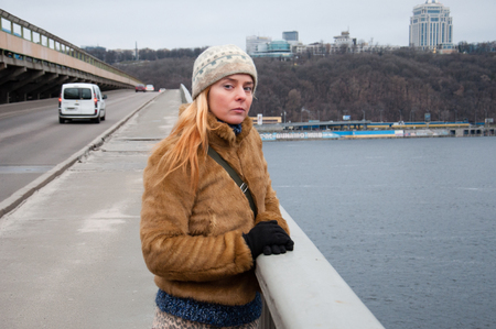 A sad woman is standing on a bridge, against the background of the city. Concept Depression