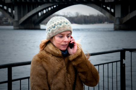 A sad woman is talking on the phone on the embankment in front of the bridge.