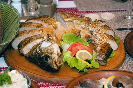 Stuffed fish with tomato, lemon, lettuce and olives
