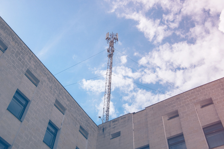 Antenna on the roof of a building against a blue sky Stock Photo