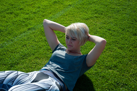 Sports fitness woman doing sports swinging a press on a green lawn outdoors on a sunny morning Stock Photo