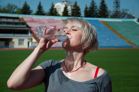 A female athlete drinks water from a bottle after training a run at the stadium
