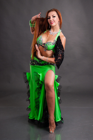 Beautiful slender woman dancing belly dance sexy Arabian Turkish oriental professional dancer in a bright, carnival shining suit with long hair.