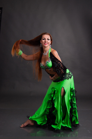 Beautiful woman dancing belly dance sexy Arabian Turkish oriental professional dancer in a bright, carnival shining suit with long brown healthy hair. Exotic belly dance star Standard-Bild
