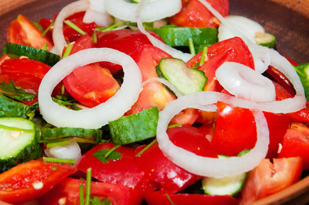 Salad of tomatoes, cucumbers, peppers, onions and greens dressed with olive, sunflower or corn oil Stock Photo