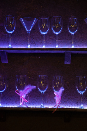 Bar, glasses of the shelf are highlighted in blue light Stock Photo