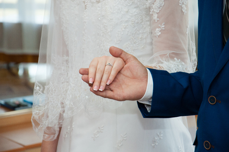 Relationship concept, love. The hands of the bride and groom. The groom holds the bride by the hand