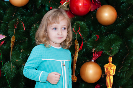 Very beautiful baby girl in a beautiful turquoise dress near the New Year tree is dreaming and smiling