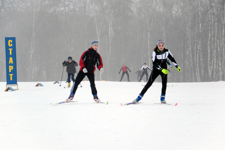 Ukraine, Chernigov, February 8, 2014: Family competitions in skiing. Two athletes, teenagers go skiing. Editorial