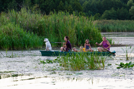 Ukraine, the city of Sednev, the river Snov, August 15, 2015: people are floating in a boat on the river, fishing at sunset, women, children, fishing.