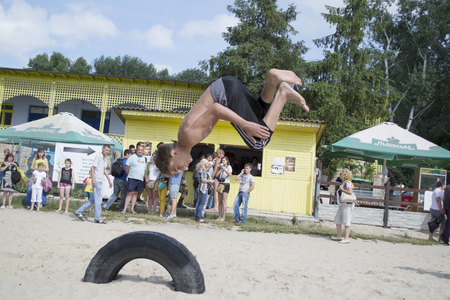 Ukraine, Chernigov, June 30, 2013: Extreme City Extreme Sports Festival. Young sports man, the guy jumps, jumps back flips with somersault in the air, parkour