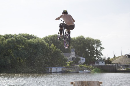 Ukraine, Chernigov, June 30, 2013: Extreme City Extreme Sports Festival. A young handsome man is jumping into the water on a bicycle from trappling.