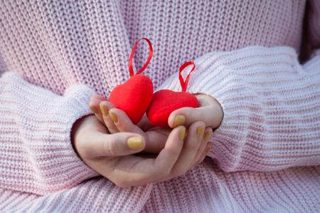 Red hearts in the hands of the girl. People, serious relationship and love concept. Valentine's day holiday 免版税图像