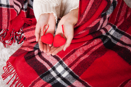 Valentines Day, two red hearts in female hands. Concept of love, feelings, relationships. Hands close up