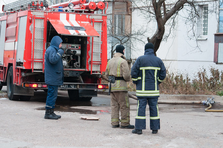 Ukraine, Chernigov, November 23, 2018: Firefighters extinguish a fire in the apartment of a nine-story building. Fire machine concept security. People, firefighters near the fire truck