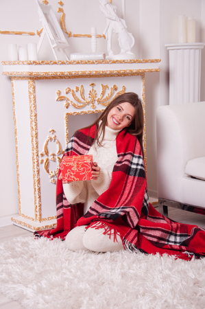 Cute beautiful young woman sitting with a gift in the room by the fireplace. Happy girl holds a gift in hands Stock Photo