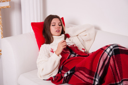 Sick woman lying on a bed with a thermometer. The girl looks at the thermometer. Severe headache, runny nose, migraine, flu, chills and fever. Concept medetsina and health Stock Photo