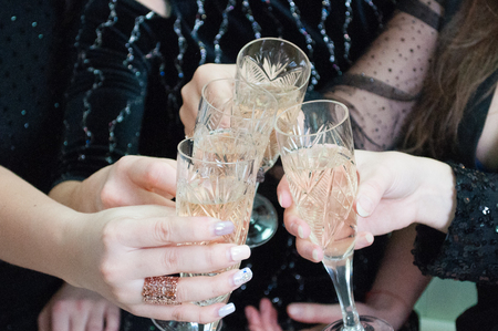 Festive glasses with champagne in female hands. Christmas celebration, birthday, hen party, wedding