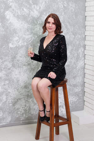 Very sexy and beautiful woman in evening chorny dress with a glass of champagne on a gray background sitting on a chair. Holiday Christmas, Birthday, Thanksgiving or Party Stock fotó