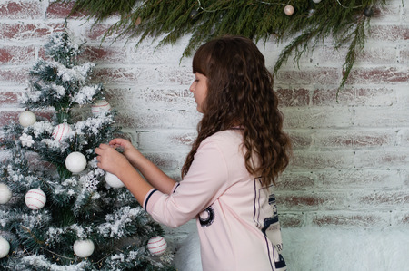 Chernigov, Ukraine November 23, 2018: Rehearsal for the celebration of the new year and Christmas. Beautiful child, teen girl near the Christmas tree in the New Year's interior.