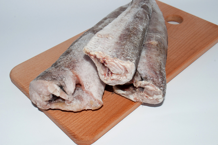 Frozen fish hake close-up on a wooden cutting board on a white background, close-up Zdjęcie Seryjne